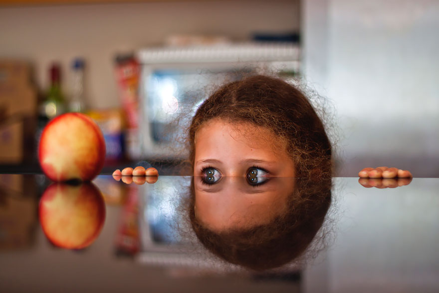 Girl Peeks At Apple On Reflective Table by Philip Cornish